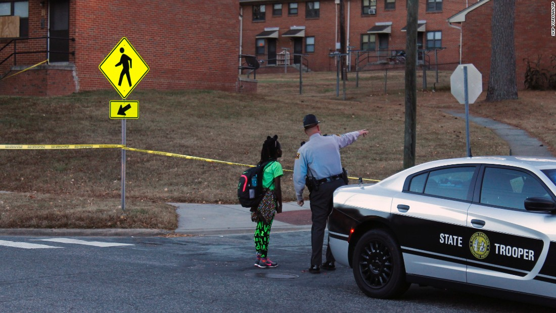 "A child gets guidance from a North Carolina state trooper after <a href=""http://www.newsobserver.com/news/local/crime/article116421508.html"" target=""_blank"">police fatally shot a man</a> at a Durham housing project on Tuesday, November 22."