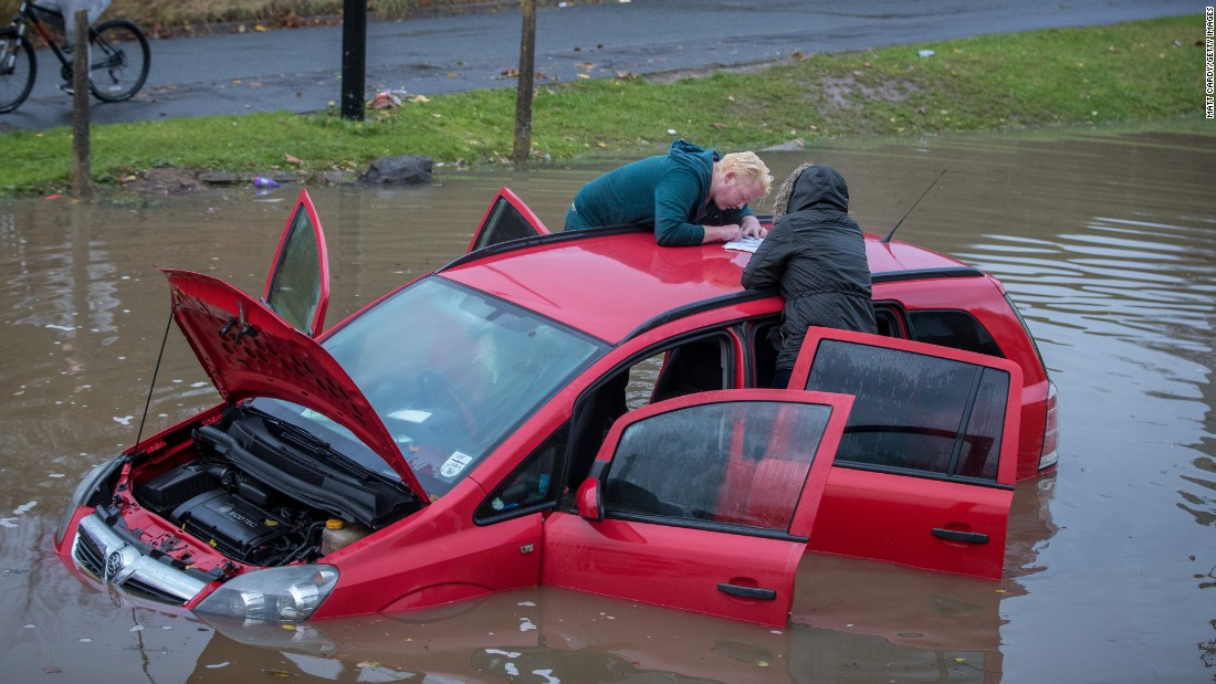 People attend to a flooded car after heavy rains in Bristol, England, on Monday, November 21.