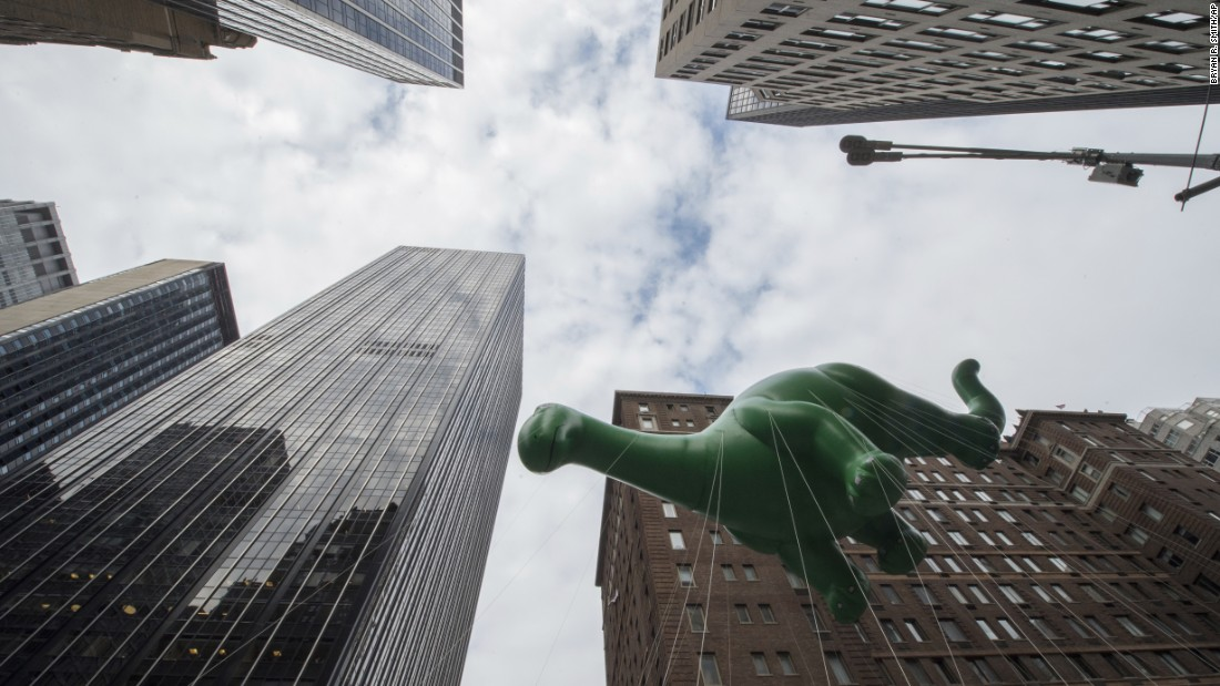 A dinosaur balloon moves down Sixth Avenue.