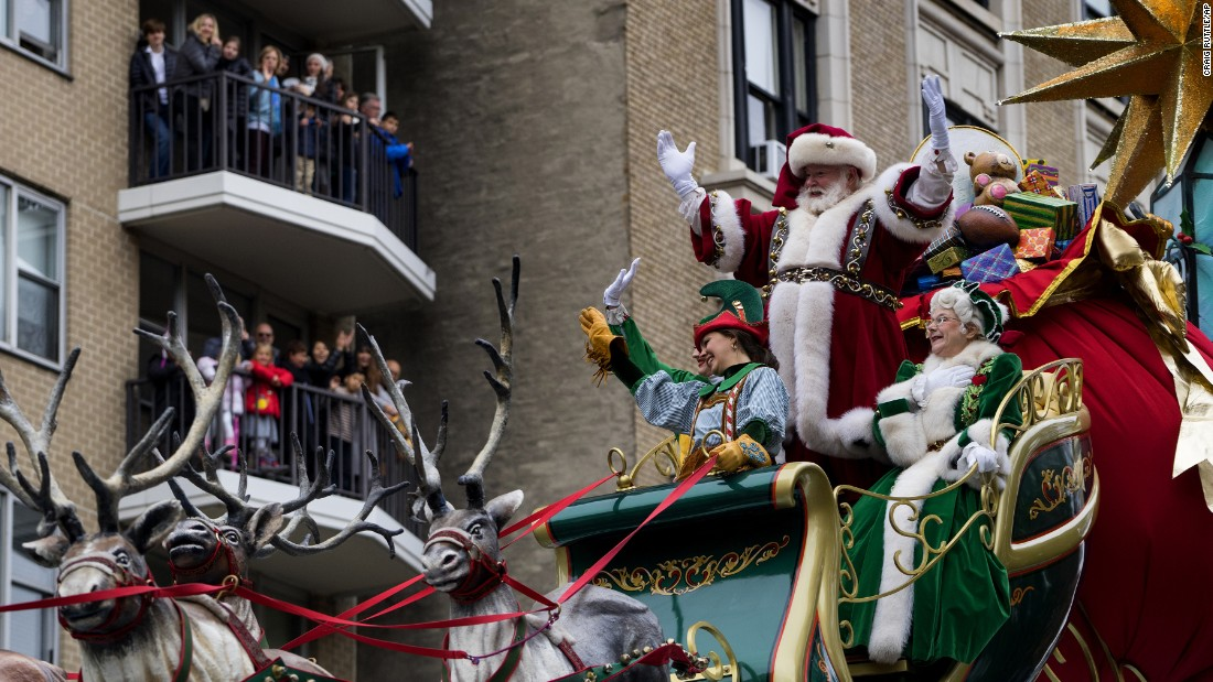 Santa Claus waves to spectators along Central Park West.