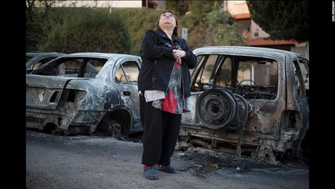 A woman looks at a damaged building next to burned cars in Haifa on November 25.