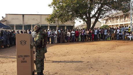 A soldier casts his ballot at a polling station as other voters wait in line, in Accra, on December 7, 2012.
