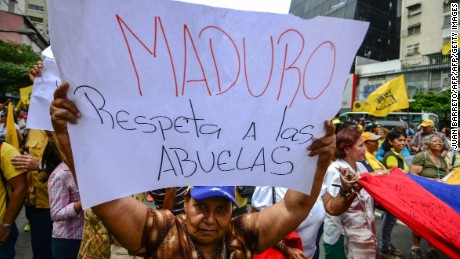 "A woman holds a sign reading ""Maduro respect grandmothers"" during an opposition protest for the delay in the pay of some pensions in Caracas on November 25, 2016. / AFP / JUAN BARRETO        (Photo credit should read JUAN BARRETO/AFP/Getty Images)"