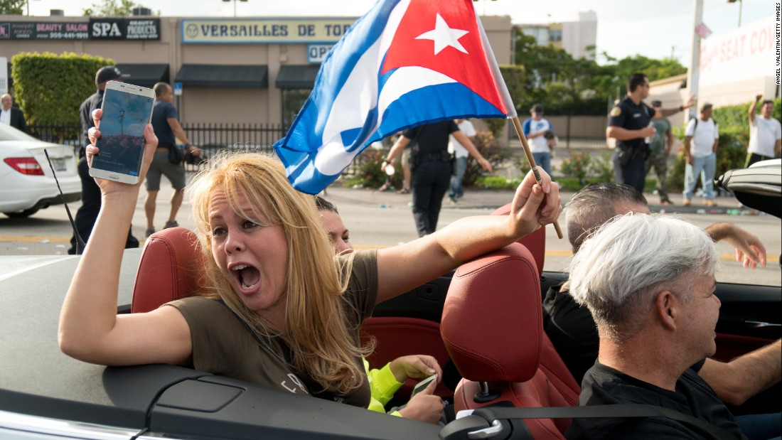 People take to the streets to react to the news of the death of former Cuban President Fidel Castro outside the restaurant Versailles in Miami.
