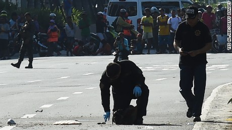Bomb disposal officers inspect an improvised explosive device in Manila on November 28.