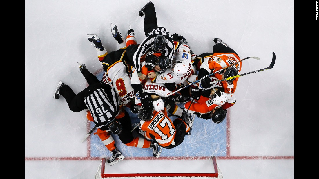Referees try to break up players during an NHL hockey game between Calgary and Philadelphia on Sunday, November 27.