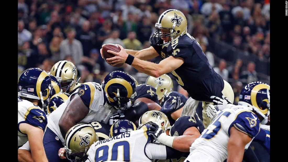 New Orleans quarterback Drew Brees dives over the pile for a first-half touchdown against Los Angeles on Sunday, November 27. Brees also threw four touchdowns in the 49-21 victory.