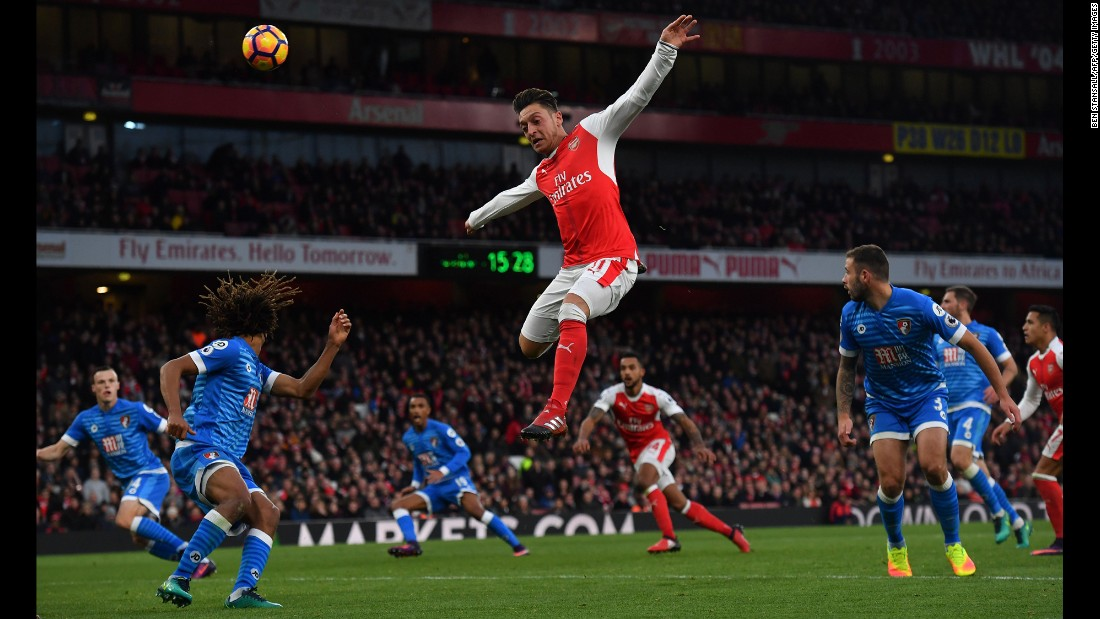 Arsenal midfielder Mesut Ozil leaps for the ball Sunday, November 27, during a Premier League match in London against Bournemouth.