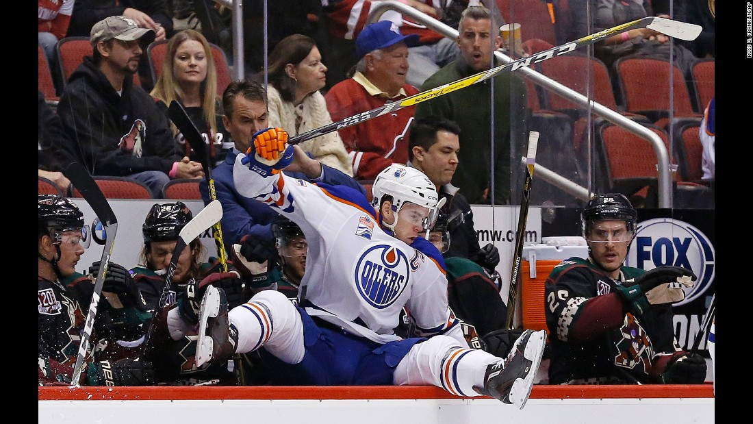 Edmonton captain Connor McDavid leaps into the opposing team's bench during an NHL hockey game in Glendale, Arizona, on Friday, November 25.