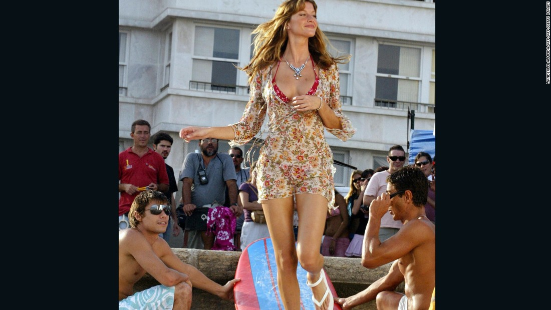 Pictured: Model Gisele walks over a surfboard during the taping of a TV commercial to promote Ipanema line of sandals bearing her name, at Ipanema Beach, Rio de Janeiro.