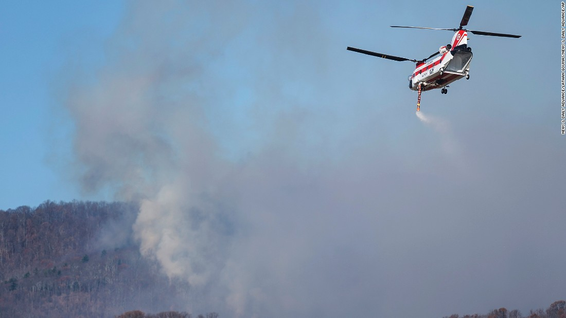 A helicopter picks up water from Thrasher Lake to help battle a wildfire in Amherst County, Virginia, on November 21.