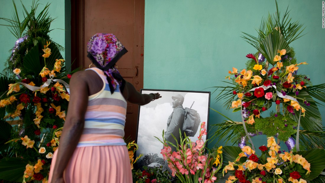 A woman stretches her hand toward a picture of Castro at a memorial in Guanabacoa, on the outskirts of Havana, on November 29.