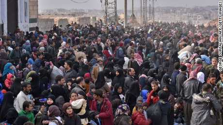 Syrians flee from eastern Aleppo on Tuesday, lining up to get onto government buses.