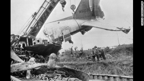 Workers watch as a large crane swings the tail section of a wrecked DC-3 onto a flatbed car at Dress Regional Airport in Evansville, Indiana, on December 16, 1977.