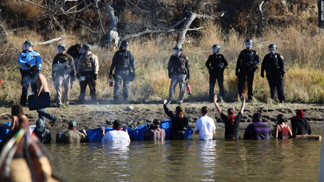 Dozens of protesters wade in cold creek waters as they confront local police on November 2.