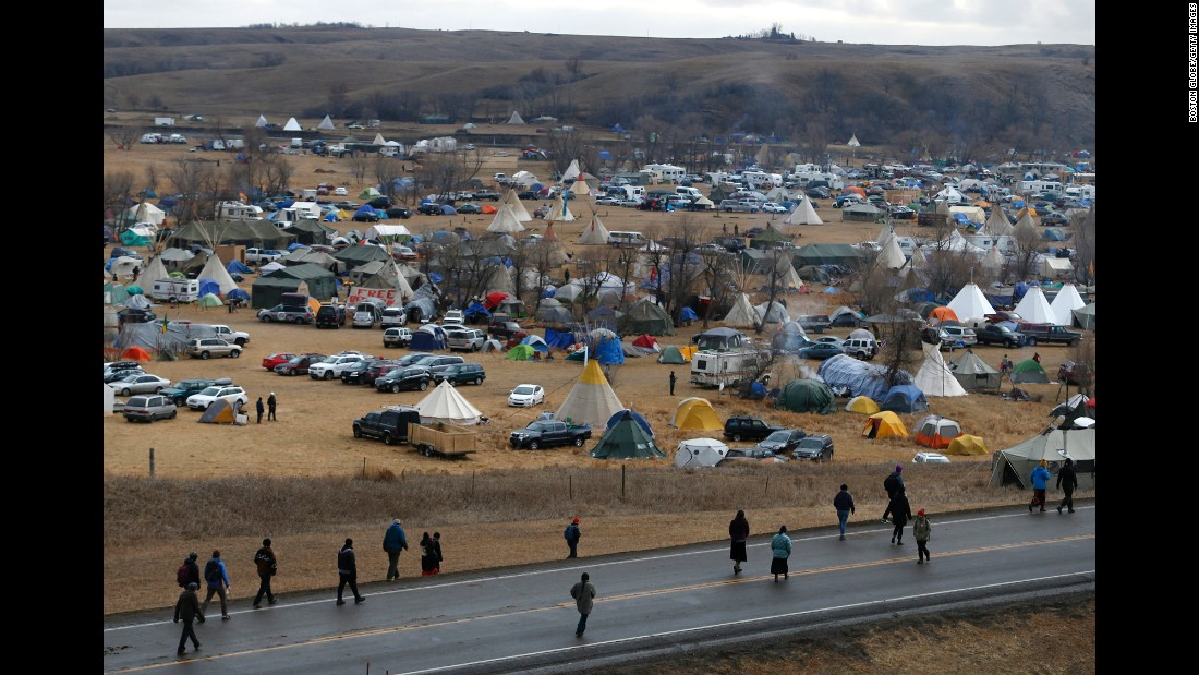 People protest along Highway 1806 as they walk past a sprawling encampment on Thursday, November 24.