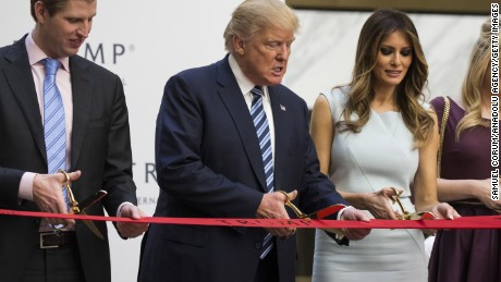 WASHINGTON, USA - October 26: Republican Presidential Candidate Donald Trump (C) cuts the ribbon with his son, Eric Trump (L), and wife, Melania Trump (R), during opening ceremony for the Trump International Hotel, Old Post Office, in Washington, USA on October 26, 2016. (Photo by Samuel Corum/Anadolu Agency/Getty Images)