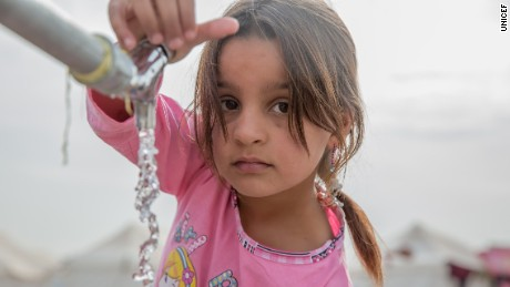 A young girl from Mosul gets water from a tap at a displacement camp in Iraq's Nineveh province.