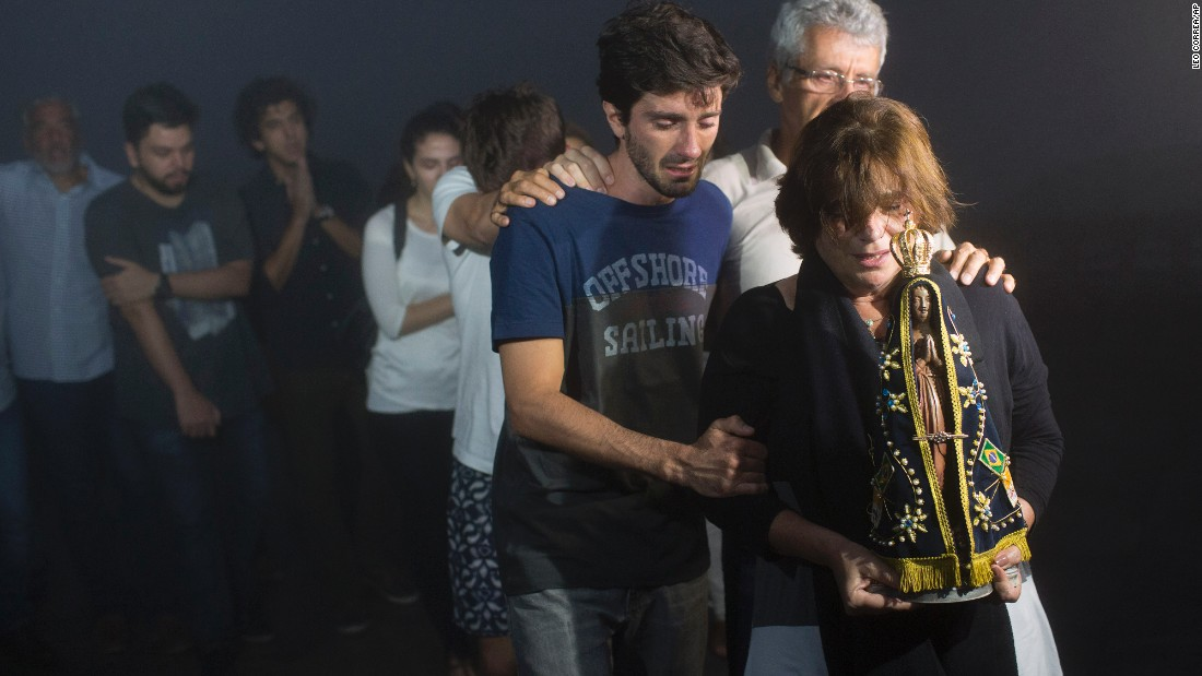 Ana Maria holds a statue of Our Lady of Aparecida as she and her family mourn the loss of her son, journalist Guilherme Marques, during a ceremony in Rio de Janeiro on November 29.