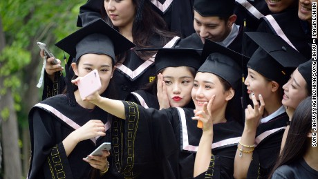 Chinese graduates dressed in academic gowns take a selfie during a photo shoot in Beijing, 23 May 2016.