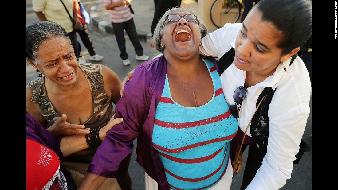 Women comfort one another after watching Castro's remains pass by in Havana on November 30.