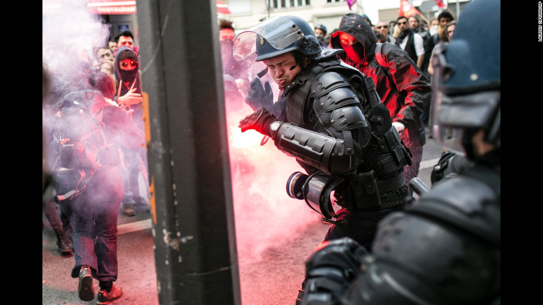 <strong>April 28:</strong> A police officer reacts during a clash with protesters in Lyon, France. People were protesting proposed reforms to the country's labor laws, and strikes forced cancellations and delays at two airports serving Paris.