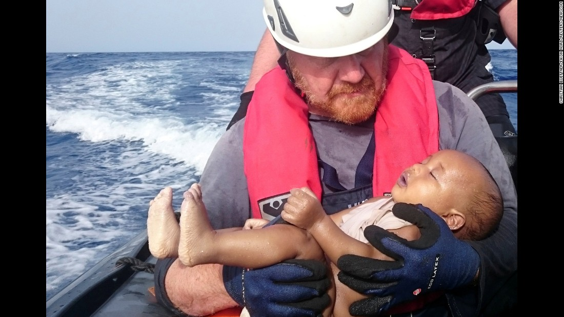 "<strong>May 27: </strong>A member of the humanitarian organization Sea-Watch holds a migrant baby who drowned after a boat capsized off the coast of Libya. The first five months of 2016 were ""particularly deadly,"" according to the U.N. refugee agency, with at least 2,510 migrant deaths through May compared to 1,855 in the same period in 2015."