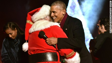President Barack Obama hugs and a man dressed as Santa Claus during the National Christmas Tree Lighting on the Ellipse of the National Mall in Washington on December 1, 2016.