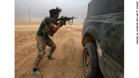 An Iraqi Shiite fighter from the Popular Mobilisation Units fires his weapon near the town of Tal Abtah, south of Tal Afar, on November 30.