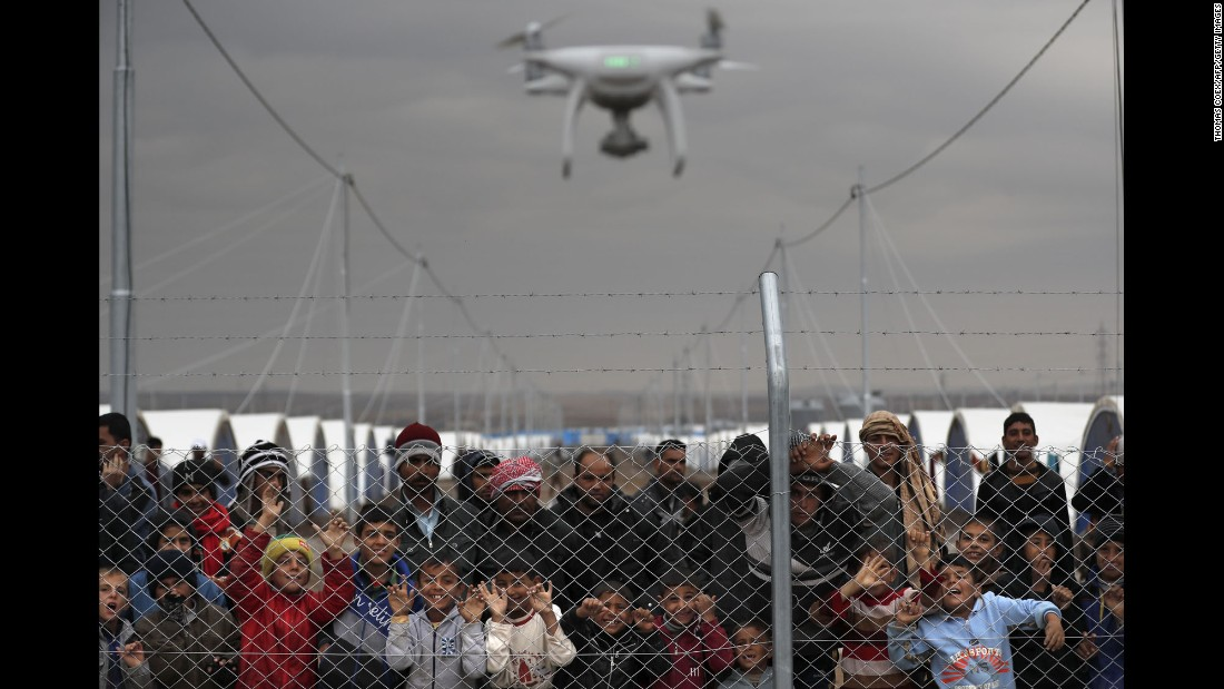 Internally displaced Iraqis who fled the fighting in Mosul watch as a civilian drone films them at the al-Khazir camp on Thursday, December 1.
