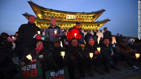 Protesters hold candles during a rally against South Korea's President Park Geun-hye in central Seoul on December 3.