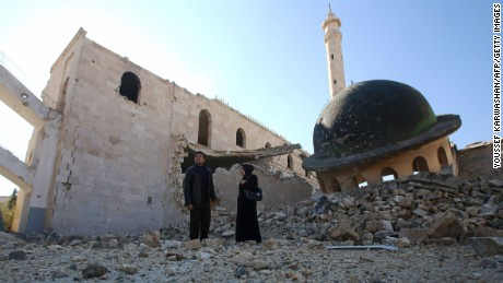 Kefa Jawish (R) and her husband Tajeddin Ahmed walk among the ruins of a destroyed mosque in Aleppo's Hanano district as they head to check their house for the first time in four years in the city's northeastern Haydariya neighbourhood on December 4, 2016.    Jawish was among hundreds of Syrians returning to east Aleppo in recent days after the army recaptured large swathes of the city from rebels and encouraged residents to visit neighbourhoods and homes they left years earlier.   / AFP / Youssef KARWASHAN / TO GO WITH AFP STORY BY RIM HADDAD        (Photo credit should read YOUSSEF KARWASHAN/AFP/Getty Images)