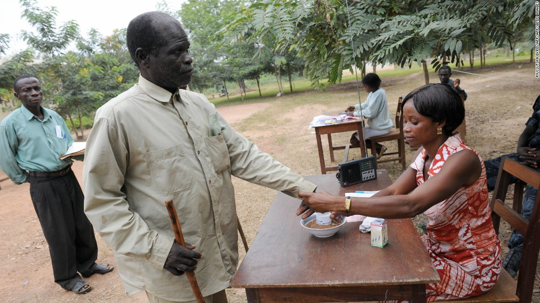 A sixty-year-old blind voter is helped by an electoral official to vote at Badu Central in Tain constituency.
