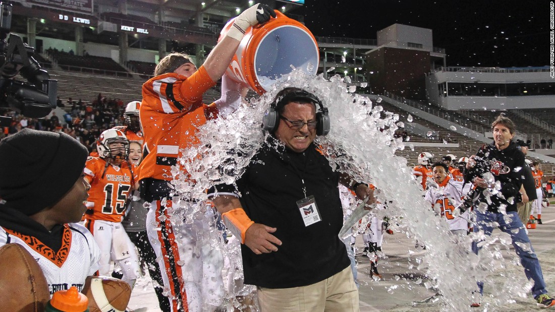 Calhoun City coach Perry Liles is doused with water after his team defeated Bay Springs 22-8 in a high school football championship game in Starkville, Mississippi, on Friday, December 2.