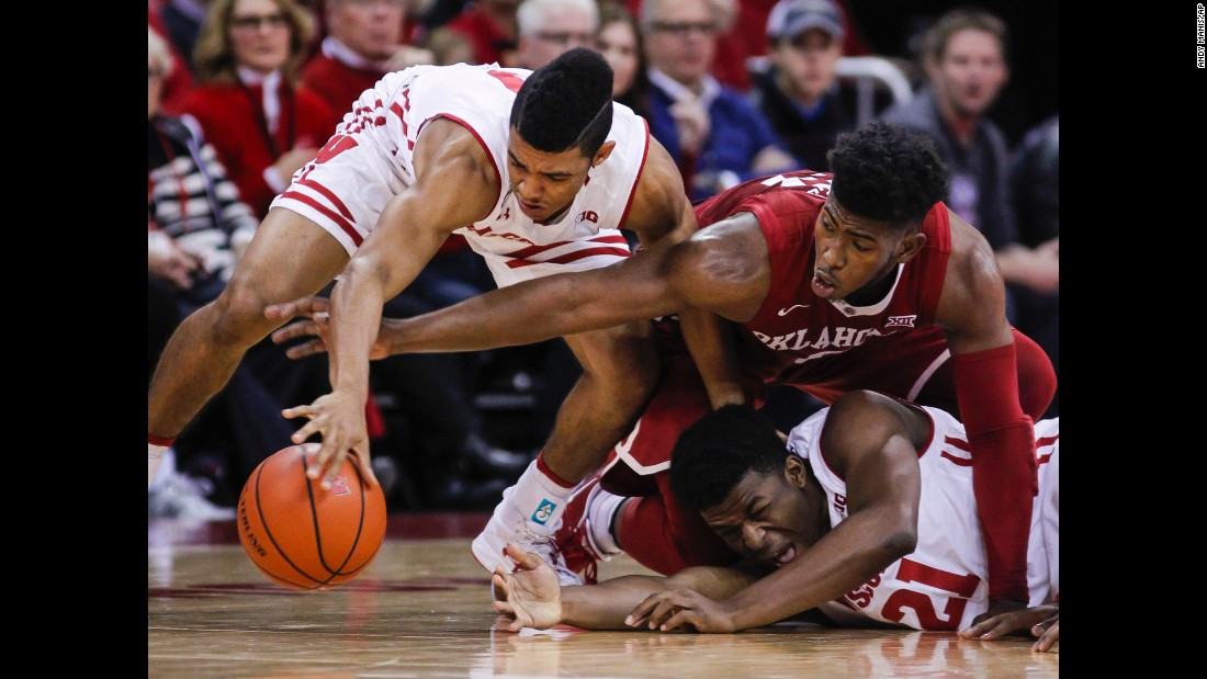 Wisconsin's D'Mitrik Trice, left, and teammate Khalil Iverson battle for a loose ball with Oklahoma's Christian James during the first half of an NCAA basketball game in Madison, Wisconsin, on Saturday, December 3. Wisconsin defeated Oklahoma 90-70.