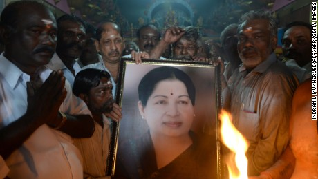 Supporters hold a photograph of Tamil Nadu state leader Jayalalithaa Jayaram as they offer prayers in Mumbai on December 5, 2016.