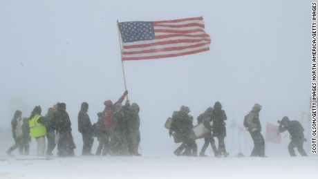 "CANNON BALL, ND - DECEMBER 05: Despite blizzard conditions, military veterans march in support of the ""water protectors"" at Oceti Sakowin Camp on the edge of the Standing Rock Sioux Reservation on December 5, 2016 outside Cannon Ball, North Dakota. Over the weekend a large group of military veterans joined native Americans and activists from around the country who have been at the camp for several months trying to halt the construction of the Dakota Access Pipeline. Yesterday the US Army Corps of Engineers announced that it will not grant an easement for the pipeline to cross under a lake on the Sioux Tribes Standing Rock reservation. The proposed 1,172-mile-long pipeline would transport oil from the North Dakota Bakken region through South Dakota, Iowa and into Illinois.  (Photo by Scott Olson/Getty Images)"