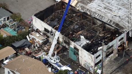 A crane lifts wreckage from the Oakland warehouse where at least 36 people died in a fire.