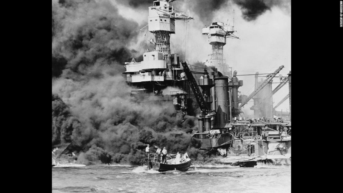A rescue boat retrieves a seaman from the burning USS West Virginia.