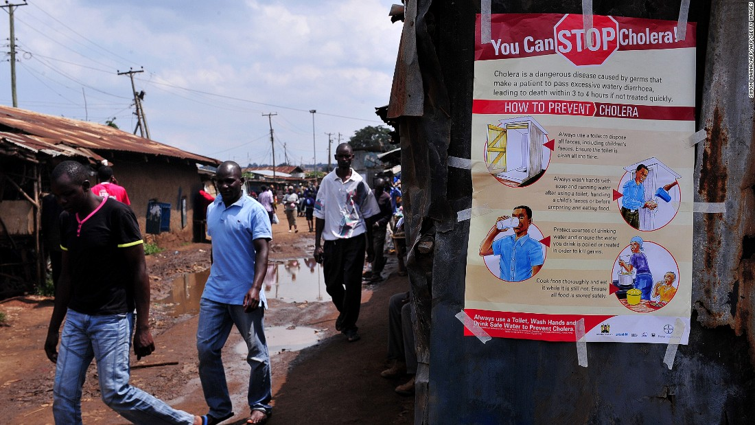 A further 76% of Kenyans believe that when children today in Kenya grow up, health care will be better.<br /><br />Pictured here, people walk past a kiosk where a poster on how to prevent Cholera is displayed in the Kibera area of Nairobi in May 2015.