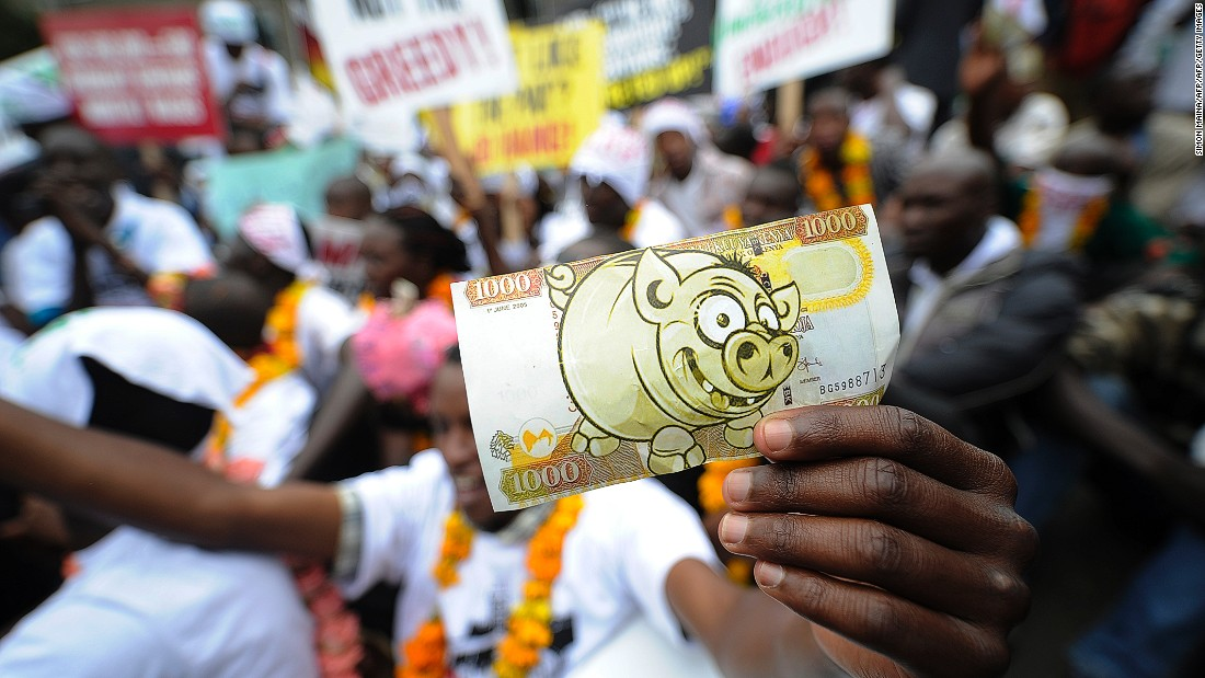 Just over half of Kenyan respondents say the national economy will improve in the next 12 months.<br /><br />Pictured here, protesters hold a fake bill imitation of local currency during a demonstration outside the parliament after lawmakers voted themselves hefty salary increases in June 2013 in Nairobi.