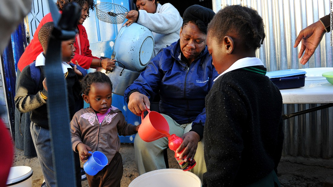 Health care is another issue just over 60% of South Africans believe will improve for their children.<br /><br />Pictured here: a mother gives out drinks to children who have lost parents to AIDS in Alexandra township in the north of Johannesburg in May 2012.