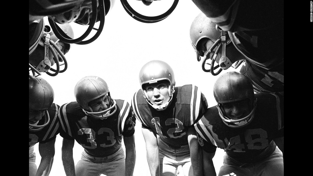 Navy quarterback Roger Staubach, No. 12, huddles with teammates during a game against the University of Pittsburgh on October 26, 1963. Staubach went on to play in four Super Bowls with the Dallas Cowboys.