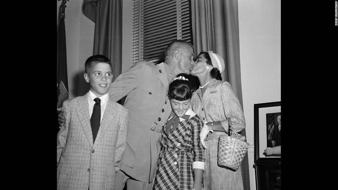 "Glenn and his wife, Annie, sandwich their daughter, Carolyn ""Lyn,"" as they embrace following a ceremony honoring his feat. Son David is at left."