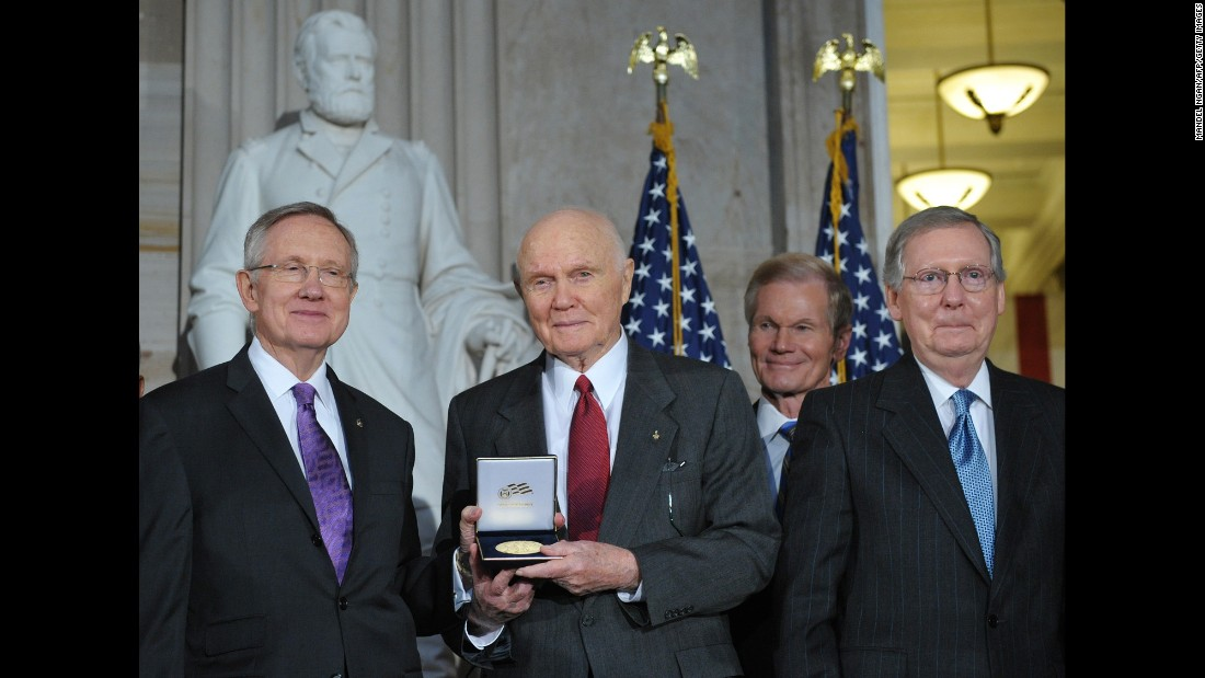 Glenn displays his Congressional Gold Medal with Sens. Harry Reid, left, Bill Nelson, second from right, and Mitch McConnell during a ceremony in the Capitol Rotunda in November 2011.