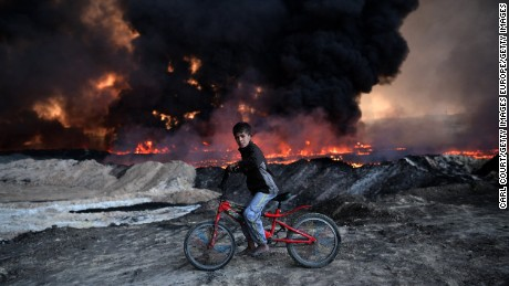 QAYYARAH, IRAQ - OCTOBER 21: A boy pauses on his bike as he passes an oil field that was set on fire by retreating ISIS fighters ahead of the Mosul offensive, on October 21, 2016 in Qayyarah, Iraq. Several hundred Iraqi families have been made to leave their homes for Mosul by Islamic State fighters as the UN warns they could be used as human shields. ISIS have attacked Kirkuk today as Kurdish and Iraqi forces, backed by a coalition including Britain and the U.S.A continue their offensive to retake Iraq's second largest city of Mosul.  (Photo by Carl Court/Getty Images)