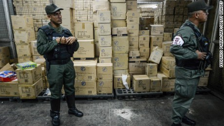 Members of the Venezuelan national guard stand next to boxes full of confiscated toys in a warehouse in Caracas on December 9, 2016. The Venezuelan government seized 3.8 million toys on December 9, 2016 from one of the country's main distributors - which it accuses of hoarding - to sell them at lower prices in poor neighborhoods.