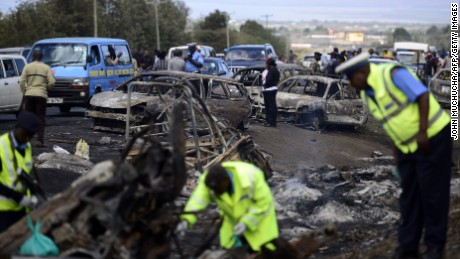 Kenyan police officers search for victims at the crash site of a truck that rammed into several vehicles before bursting into flames.
