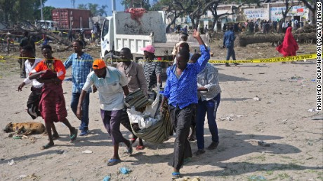 People carry the body of a victim at the scene of a car bomb attack near the port of the capital Mogadishu, on December 11, 2016. More than 20 people were killed on December 11 in a suicide truck bombing in the Somali capital Mogadishu, police said, in a fresh strike claimed by the Al-Qaeda-linked Shabaab group.