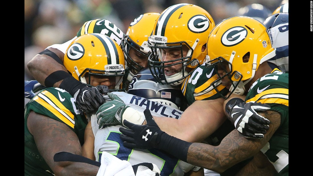 Several Green Bay Packers tackle Seattle running back Thomas Rawls during an NFL football game in Green Bay, Wisconsin, on Sunday, December 11. The Packers blew out the Seahawks 38-10.
